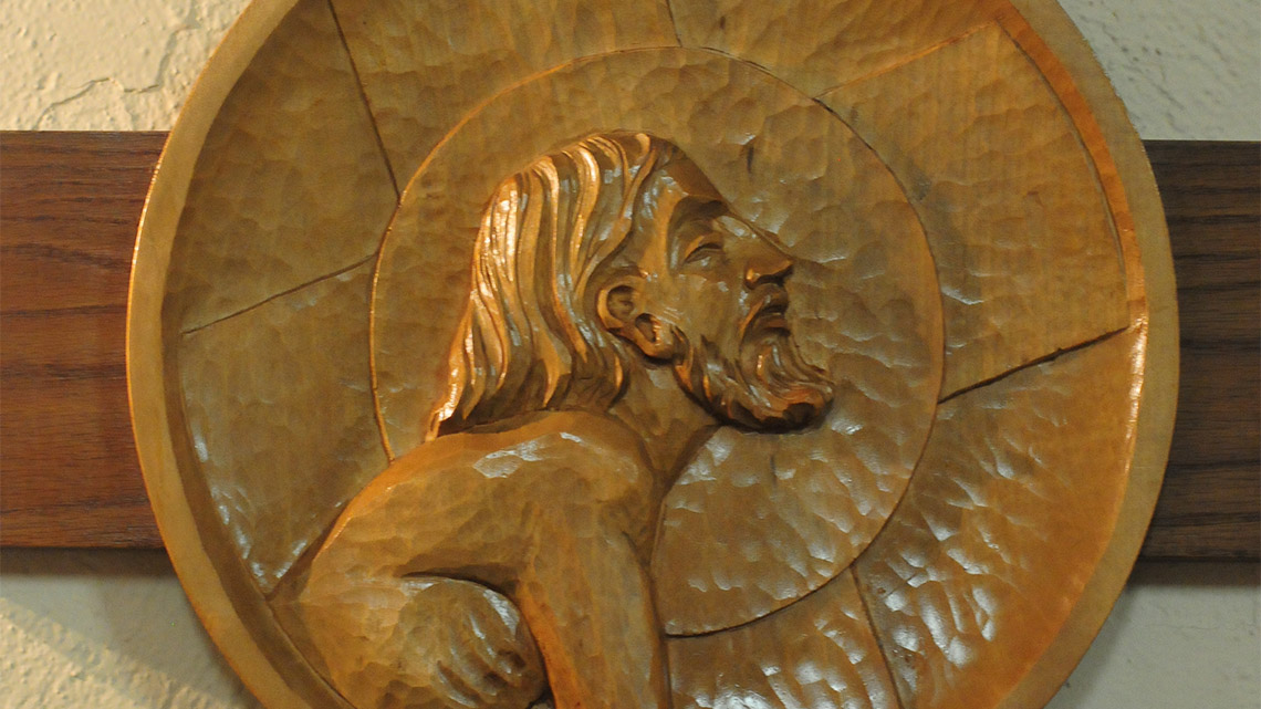 Christ depicted at one of the Stations of the Cross. Each station is a circular relief carving in wood.