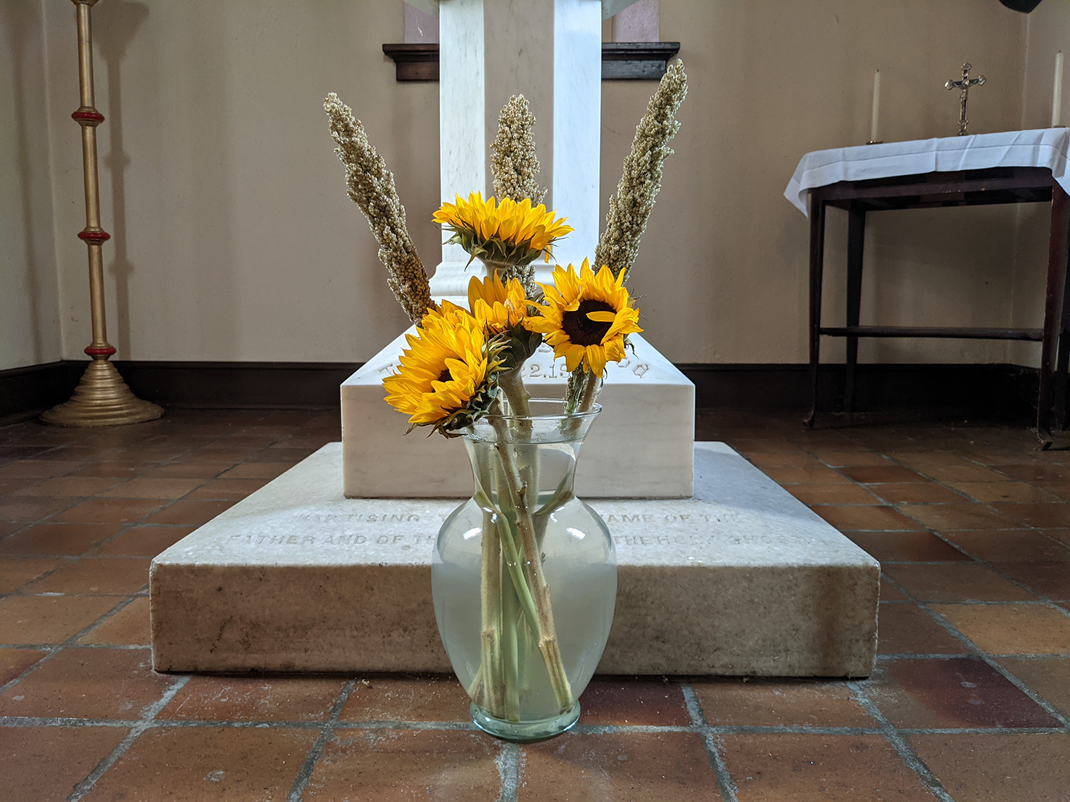 Sunflowers in a vase at foot of font